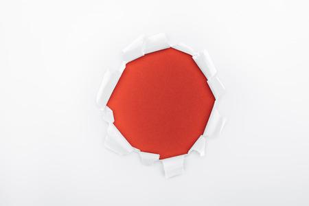 Foto de ripped hole in textured white paper on red background - Imagen libre de derechos