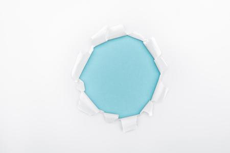 Foto de torn hole in textured white paper on blue background - Imagen libre de derechos