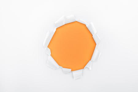 Foto de ripped hole in textured white paper on orange background - Imagen libre de derechos