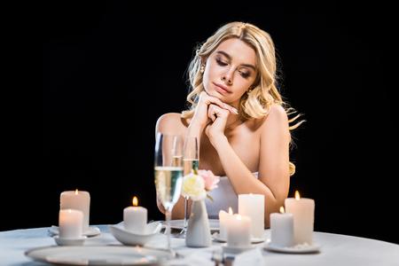 Foto de dreamy young bride sitting by served table alone isolated on black - Imagen libre de derechos