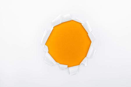 Foto de ragged hole in textured white paper on orange background - Imagen libre de derechos