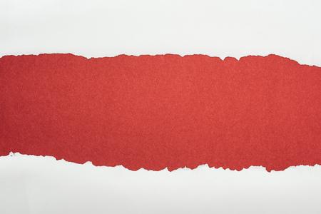 Foto de ragged white textured paper with copy space on burgundy background - Imagen libre de derechos