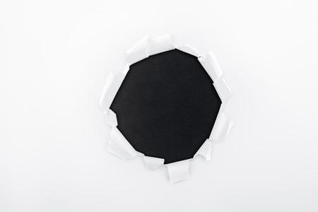 Foto de ragged hole in textured white paper on black background - Imagen libre de derechos