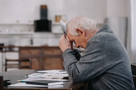 Foto de stressed senior man in casual clothes sitting at table with paperwork and holding money at home - Imagen libre de derechos