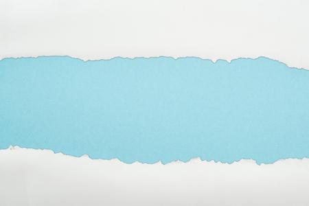 Foto de ragged white and textured paper with copy space on light blue background - Imagen libre de derechos