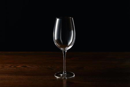 Foto de Empty wine glass on wooden surface isolated on black - Imagen libre de derechos