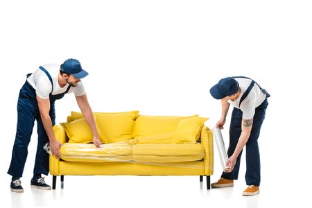 Foto de two movers wrapping yellow sofa with roll of stretch film on white - Imagen libre de derechos