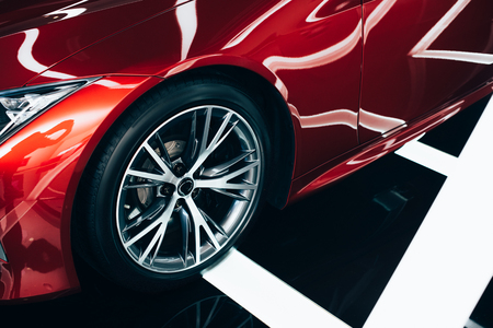 Foto de shiny new red automobile with metallic wheel in car showroom - Imagen libre de derechos