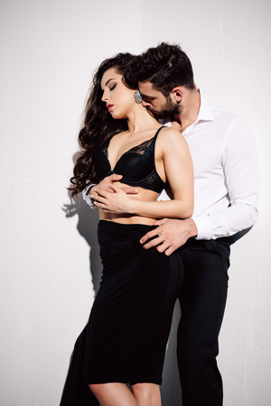 Photo pour handsome man kissing neck of beautiful woman in black dress on white - image libre de droit