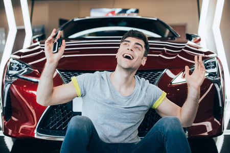 Photo pour happy excited man sitting near new car in car showroom - image libre de droit