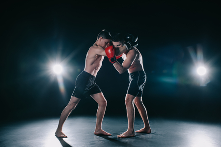 Photo pour shirtless muscular boxers in boxing gloves standing in clinch - image libre de droit