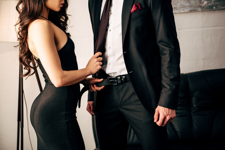 Photo for cropped view of sexy girl in black dress holding tie of man - Royalty Free Image