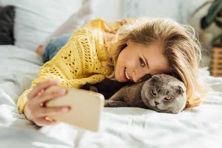 Foto de beautiful smiling young woman taking selfie on smartphone while lying in bed with scottish fold cat - Imagen libre de derechos