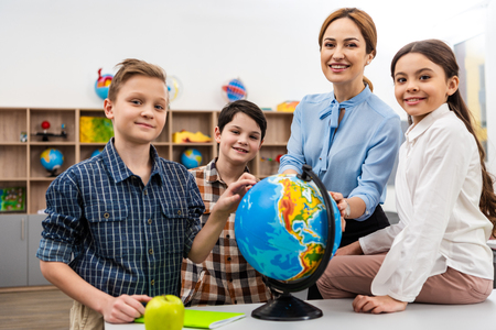 Photo pour Teacher and pupils touching globe with smile while studying geography in classroom - image libre de droit