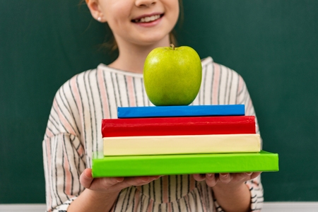 Photo pour Cropped view of cheerful ginger shoolgirl holding books and green apple in front of blackboard in classroom - image libre de droit