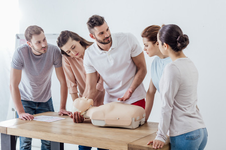 Foto de group of people with cpr dummy during first aid training class - Imagen libre de derechos