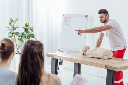 Photo pour handsome instructor with cpr dummy pointing with finger during first aid training class - image libre de droit