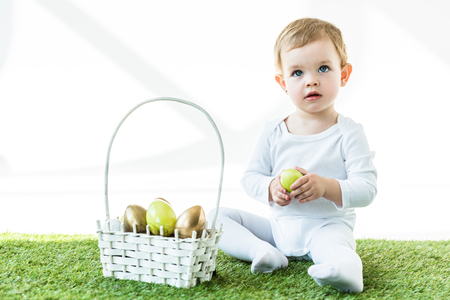 Photo pour cute blonde baby holding yellow chicken egg while sitting near straw basket with Easter eggs  isolated on white - image libre de droit