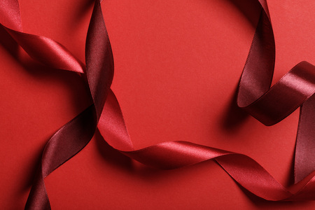 Foto de close up of curved silk burgundy and red ribbons on red background - Imagen libre de derechos