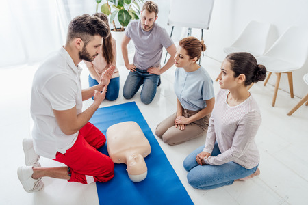 Photo pour handsome instructor gesturing during first aid training with group of people - image libre de droit