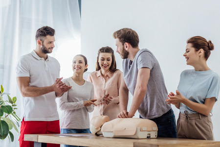 Foto de group of people applauding while man performing cpr on dummy during first aid training - Imagen libre de derechos