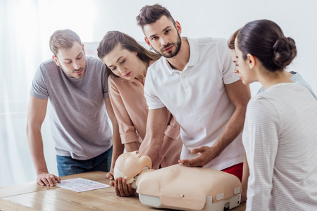 Foto de man holding cpr dummy and looking at camera during first aid training class with group of people - Imagen libre de derechos