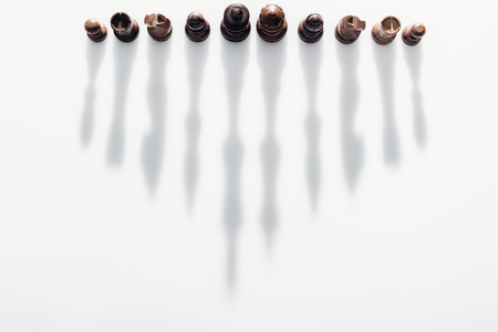 Photo pour top view of brown chess figures with long shadows on white background - image libre de droit