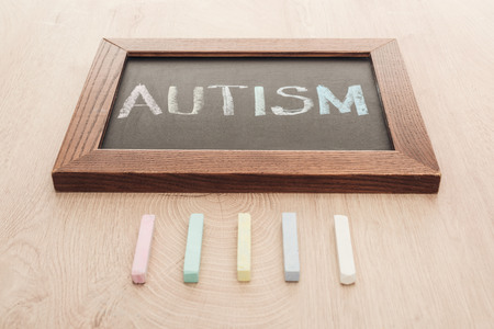 Foto de autism lettering written on chalkboard near multicolored chalks on wooden surface - Imagen libre de derechos