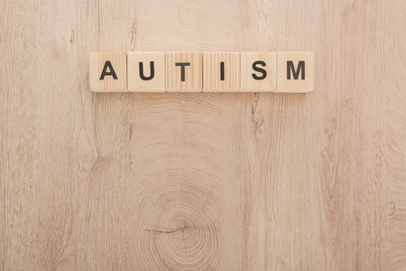 Foto de top view of autism lettering made of cubes on wooden table - Imagen libre de derechos