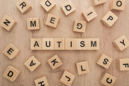 Foto de top view of autism lettering made of wooden cubes with different letters on wooden table - Imagen libre de derechos