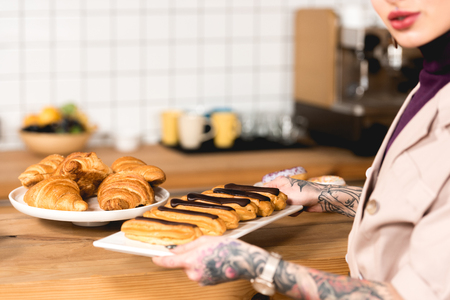 Photo for cropped view of cafe owner placing dish with eclairs on bar counter in coffee shop - Royalty Free Image