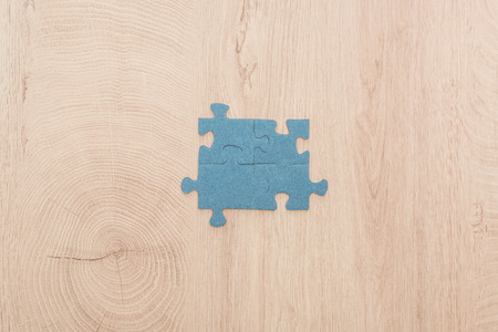Foto de top view of blue puzzle pieces connected on wooden table - Imagen libre de derechos