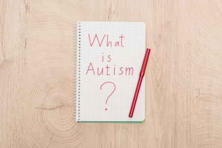 Foto de top view of red marker and what is autism question written in notebook on wooden table - Imagen libre de derechos