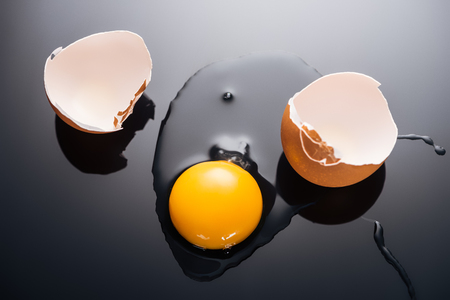 Photo for close up of fresh smashed egg with yolk, protein and eggshell on black background - Royalty Free Image