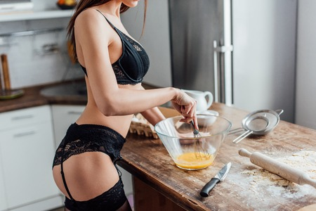 Foto de Cropped view of sexy woman in black lingerie whipping eggs with whisk in kitchen - Imagen libre de derechos