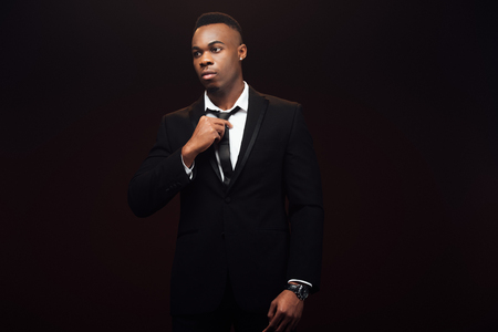 Photo pour Handsome fashionable African American man in suit adjusting tie isolated on black background - image libre de droit