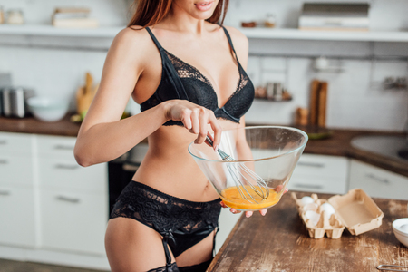 Foto per Cropped view of sexy woman in black lingerie whipping eggs with whisk in kitchen - Immagine Royalty Free