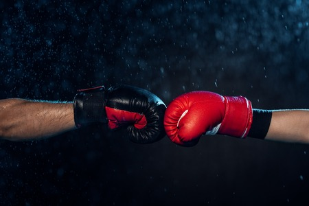 Photo pour Partial view of two boxers in boxing gloves touching hands on black background - image libre de droit