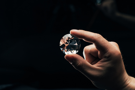 Photo pour Partial view of man holding big clear shiny diamond on black background - image libre de droit