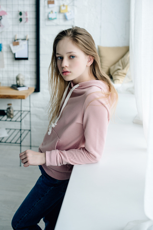 Photo pour Teenage kid in pink hoodie standing near window sill - image libre de droit