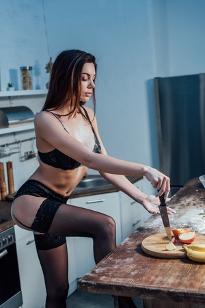 Foto per Sexy girl in black lingerie with knife in kitchen - Immagine Royalty Free