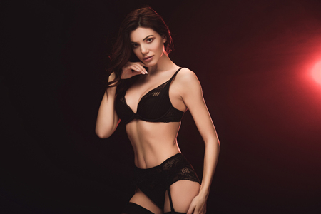 Photo pour Beautiful seductive woman in lace lingerie looking at camera on black with red light background - image libre de droit
