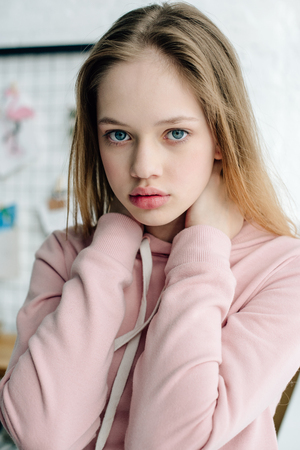 Foto de Teenage child in casual pink hoodie looking at camera - Imagen libre de derechos