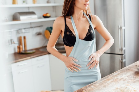 Foto per Cropped view of sexy woman in black underwear wiping hands with apron in kitchen - Immagine Royalty Free