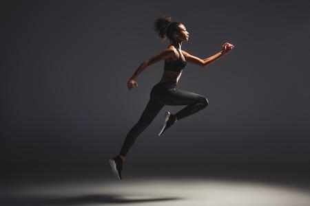 Foto de Side view of beautiful athletic African American sportswoman jumping on black background - Imagen libre de derechos