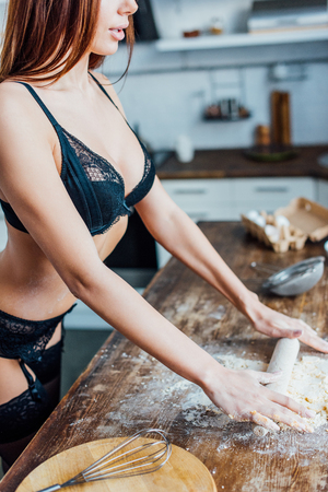 Foto per Cropped view of sexy woman in black lingerie rolling out dough with rolling pin - Immagine Royalty Free