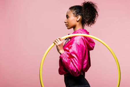 Photo pour side view of beautiful african american sportswoman posing with hula hoop isolated on pink with copy space - image libre de droit