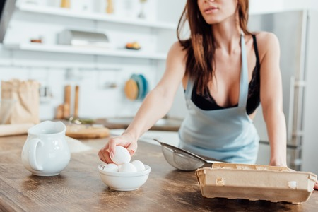 Foto per Cropped view of sexy woman in underwear and blue apron holding eggs in kitchen - Immagine Royalty Free