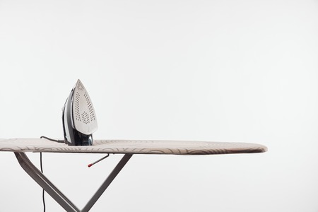 Photo for Ironing board with dark legs and iron isolated on white background - Royalty Free Image