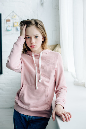 Photo pour Teenage kid in pink hoodie standing near window sill and touching hair - image libre de droit